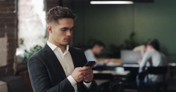 Young businessman in a suit using smartphone standing in modern office. Man looking into the camera. Workers in the background