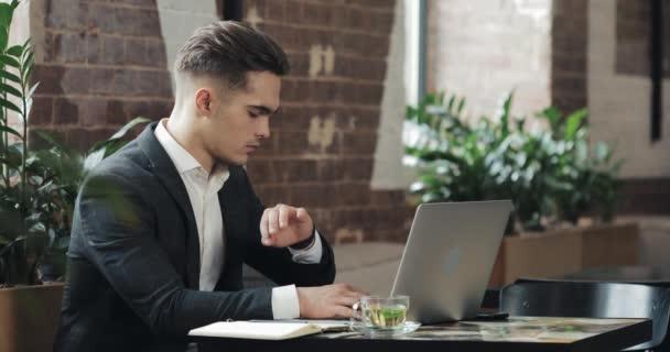 Mladý podnikatel v moderní kanceláři nebo společně pracovat a pomocí chytré hodinky. Volné noze mluví s smartwatch 4k Uhd