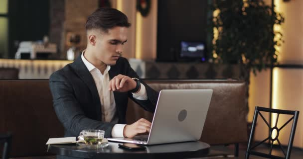 Young businessman working in modern office or co-working and using smart watch. Freelancer talking to a smartwatch 4K UHD