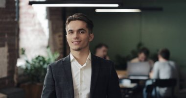 Portrait of young successful businessman at busy office. Handsome male employee looking at camera and smiling. Business, Finance, Founder, Success Concept