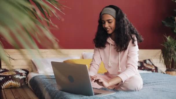 Gyönyörű lány öltözött rózsaszín pizsama, laptop számítógéppel ült az ágyban otthon. Fiatal nő mosolyog