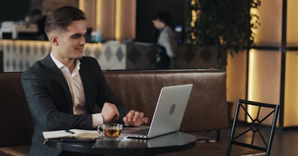 Smiling businessman using laptop computer sitting at the cafe table