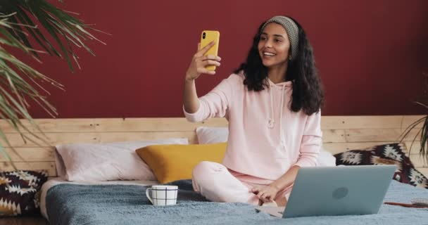 Happy african american girl sitting on the bed at homec hatting with her friends on a video call on her yellow smartphone