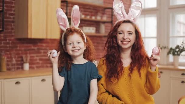Vicces portréja a boldog anya és vele a kis lányom játszik a húsvéti tojás. Nyuszi füle a kamerába nézett, boldog család