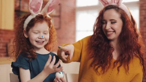 Frohe Ostern. Die junge Mutter und ihre kleine Tochter bemalen sich gegenseitig Eier und Gesichter. Familienwitze