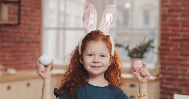 Portré, vidám vörös kis gyerek lány, nyuszi füle egy húsvéti tojás a konyhai háttérrel. Ő ujjongott, és birtoklás móka a kamerát. Kellemes húsvéti ünnepeket