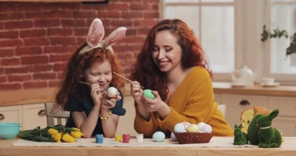 Boldog húsvétot! Anya és a kislánya tojásokat festenek. Boldog család készül húsvétkor. Nyuszifül van rajtuk.