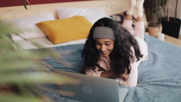 Boldog afro-amerikai lány fekszik az ágyon, boldogan beszélgető-val barátaival a videohívás rajta laptop, lassított ablak hasát