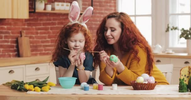 Happy easter. Mom and her little daughter are preparing for Easter. happy family painting Easter eggs in cozy kitchen. Little girl wearing bunny ears