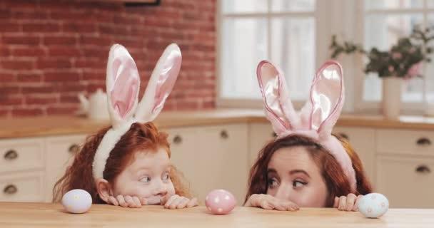 Kellemes húsvéti ünnepeket. Fiatal anya és lánya nézett a kamerába, és kezdjük el vadászat for húsvéti tojás viselése Nyuszifül. Boldog család készül a Húsvétra a kényelmes konyha