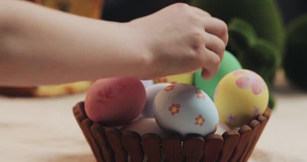 Zár-megjelöl-a anya és lánya kezét fel húsvéti tojást egy kosárban. Húsvét. Előkészítése a húsvéti party