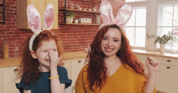 Frohe Ostern. fröhliche rothaarige kleine Mädchen mit ihrer Mutter trägt Hasenohren macht Videochat mit Verwandten oder Freunden. sie winken Hände, reden und haben Spaß in die Kamera