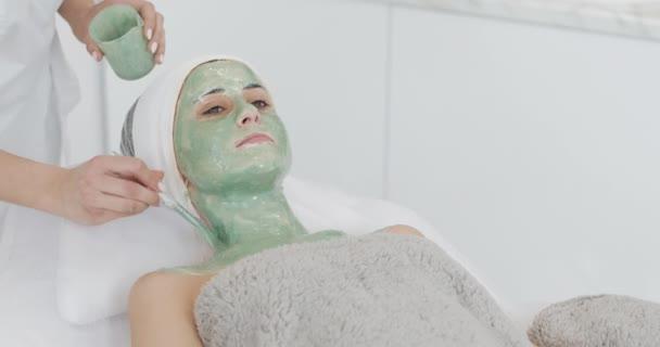 schöne junge Mädchen bei der Kosmetikerin macht die Wellness-Verfahren. Eine Hand des Kosmetikers trägt eine grüne Maske auf das Gesicht des Patienten auf. Konzept der Körperpflege gesunder Lebensstil