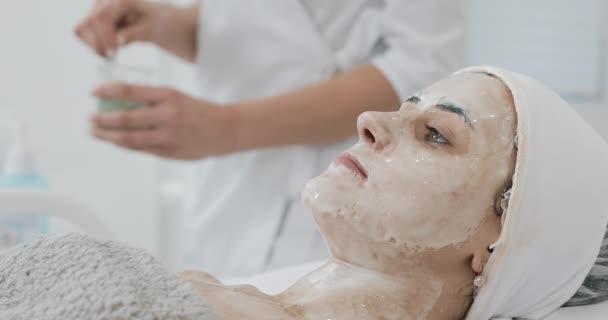 Kosmetikerin setzt Patienten im Wellness-Salon eine weiße Maske auf. Konzept der Körperpflege gesunder Lebensstil
