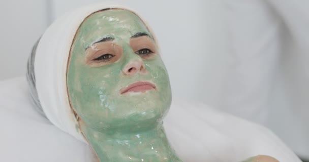 Frau im Wellnesssalon. Gesichtsmaske. schönes Mädchen auf der Couch liegend mit grüner Maske in der Klinik für Kosmetologie