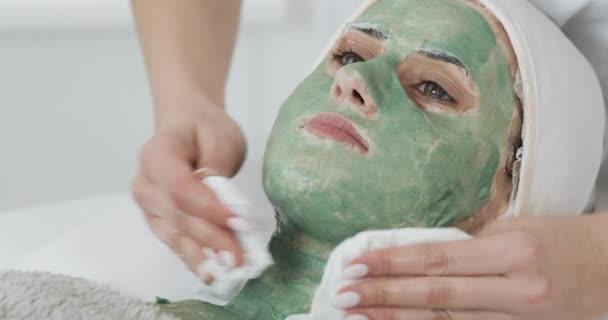 Gyönyörű fiatal lány a kozmetikus nem a gyógyfürdő eljárásokat. A nő mosott ki a zöld maszk