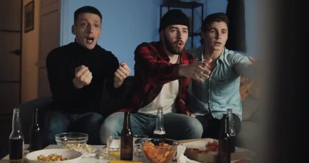 Három jó barát néz labdarúgó-mérkőzés a TV-otthon, ujjongó legjobb futballcsapat. Érzelem. Férfi rajongók ünnepelni győztes.