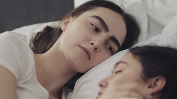 Lesbian couple hugging and smiling while lying together in bed at home. Young lesbians kisses and hugs after wake up