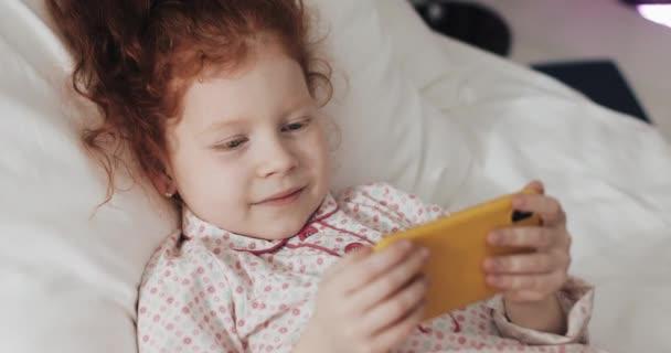 lustiges rothaariges kleines Mädchen, das im Bett liegt und interessiert Video auf modernem gelben Smartphone anschaut.