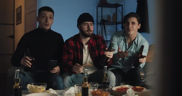 Drei Fußballfans sind für ihre Lieblings-Fußballmannschaft zu Hause durch den TV verwurzelt. Männer trinken Bier und essen Pizza. Fröhliche Stimmung, Spaß haben.