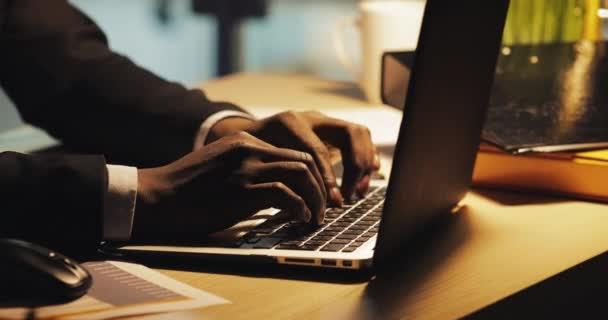 Uzavření obchodníka pomocí přenosného počítače přesčas v noci. Ruce na volné noze používající přenosný počítač
