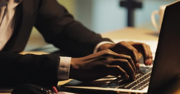 Tired young black businessman typing on laptop computer. He working at night office. Steadicam shot.