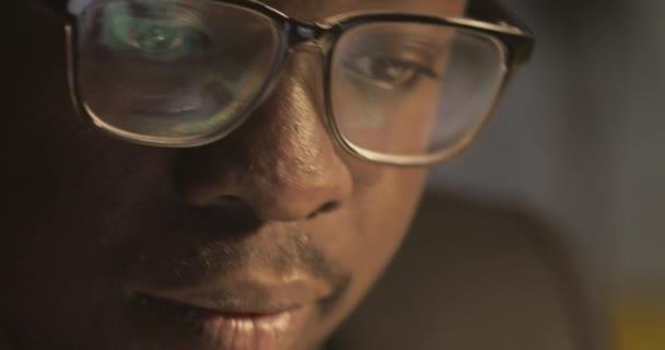 Koncentrált afro-amerikai üzletember szemüvegek előtt laptop tükrözi a kijelző szemüvegek. Fiatal férfi szabadúszó dolgozik éjjel-Time. Közelről.
