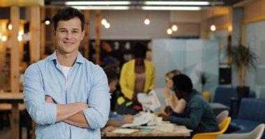 Portrait of young smiling successful businessman standing in modern office. Working people on the blurred background.