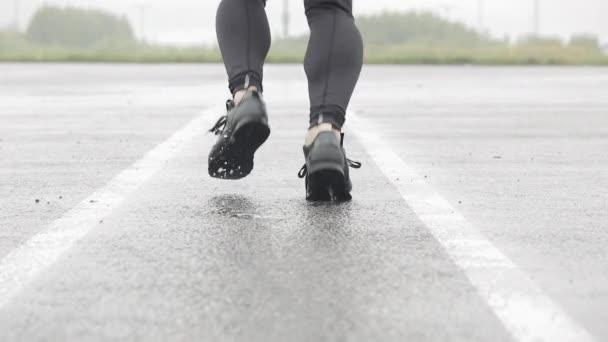 Zeitlupenaufnahme von Beinen eines Läufers in Turnschuhen. männlicher Sportler beim Joggen im Freien. Einzelläufer bei regnerischem Wetter. Nahaufnahme.