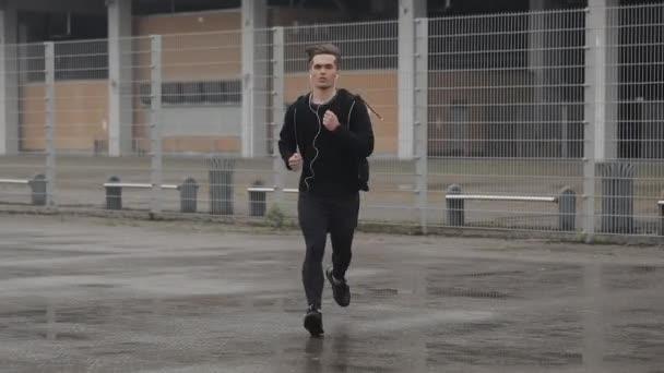 Giovane attraente che corre allaperto indossando auricolari al rallentatore. Pioggia. Esercizio cardio. Stile di vita sano - corsa.