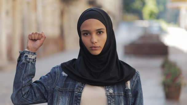 Women resist symbol. Young Muslim woman wearing hijab headscarf make fist up gesture standing on the old street background.