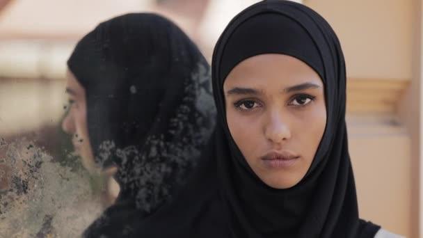 Porträt einer wütenden jungen Muslimin mit Hidschab-Kopftuch, die vor dem Hintergrund der Altstadt in die Kamera blickt. Eine Frau bereitet sich auf einen Terroranschlag vor