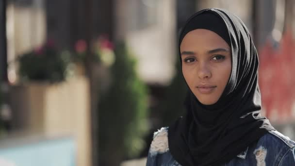 Portrait of beautiful young Muslim woman wearing hijab headscarf looking into the camera standing on the old city background.