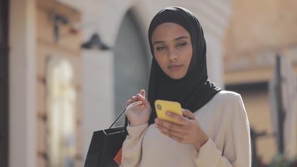 Portré boldog fiatal muszlim nő hidzsáb állt okostelefon az utcán bevásárló táskák a kezében. Online vásárlás, Shopaholic koncepció,