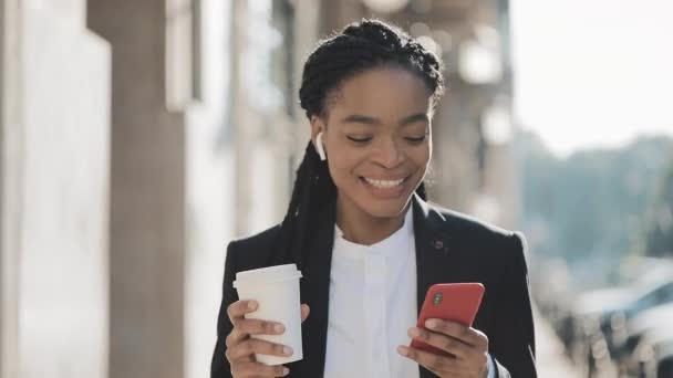 Portrait of a young African American businesswoman in a suit, walking around the city, drinking coffee and using smartphone. Concept: new business, communication, work day, freelancer.