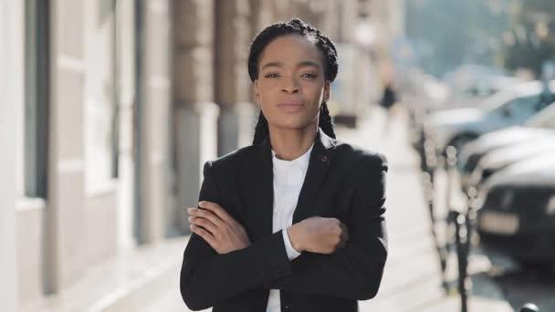 Portréja mosolygó afro-amerikai üzleti nő állt a régi utcán, és átkelés kezét. Ő nézte a kamerát, és mosolyogva. Fekete stílusos. Raszta. Afro frizura.