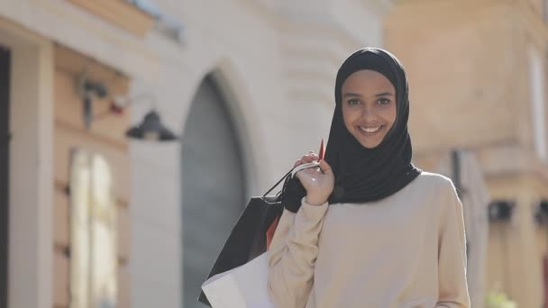 Portrait of happy young muslim woman in hijab standing down the street with shopping bags in her hand. Online shopping, shopaholic concept.