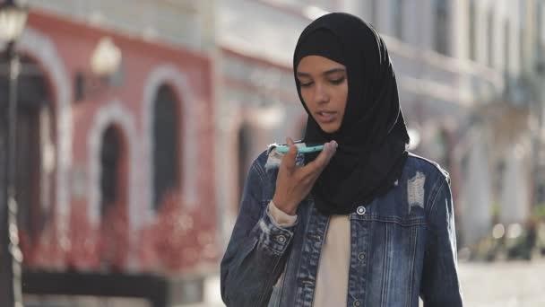 Fiatal muzulmán asszony elküldés audio hang üzenet-ra cellphone-on szabadban történő beszélő-hoz mozgatható segéd-. Lány használ smartphone hangfelismerés, diktálja gondolatait, hangtárcsázás üzenet