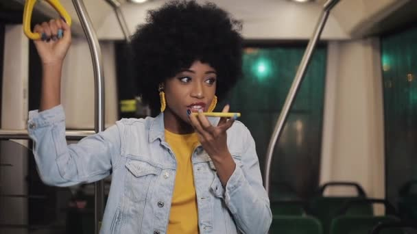 Photo Young african american woman using smart phone voice recognition, dictates thoughts, voice dialing message riding in the public transport.