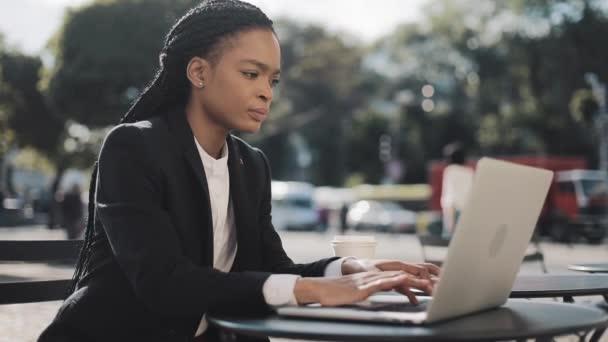 African American fiatal nő dolgozik a laptop ülve kávézóban a nyári teraszon. Üzleti, munka-, szabadúszó koncepció.