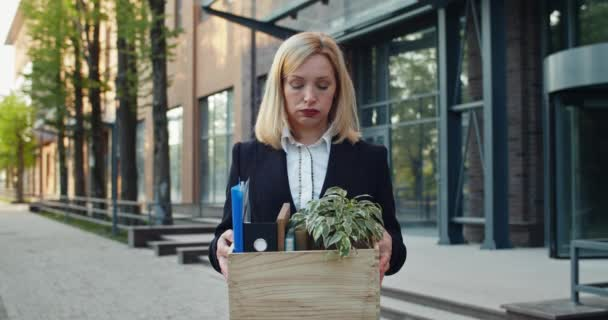 Confused woman in formal suit holding box with her stuff and looking aside. Embarassed female worker making deep breath while standing near modern office and started moving on.