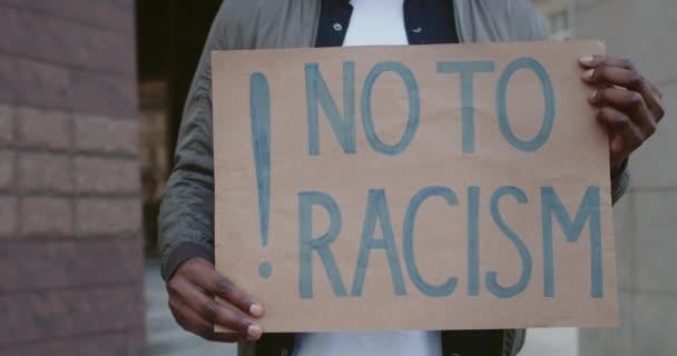 Oříznout pohled na africké americké mužské ruce držící kartónový plakát bez rasismu na ulici. Koncept lidských práv a rasové nerovnosti.