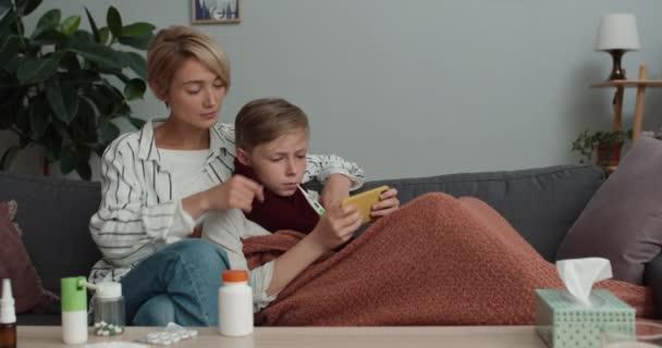 Teen boy bedeckte Decke zur Temperaturmessung und Online-Spiel auf dem Smartphone, während er sich auf seine Mutter lehnt.Schöne Frau und ihr kranker Sohn sitzen auf der Couch zu Hause.