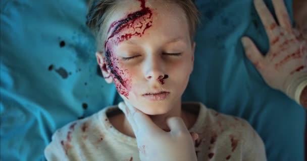 Zraněný chlapec po nehodě otevřel a zavřel oči, když ležel na nemocničním nosítkách v sanitce. Pohled shora na dítě s krví a ranou na hlavě, jak jede se záchranáři na kliniku.