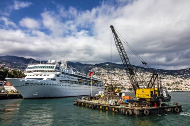 Luxury Yacht and trash barge in sea port of Funchal, Madeira island, Portugal