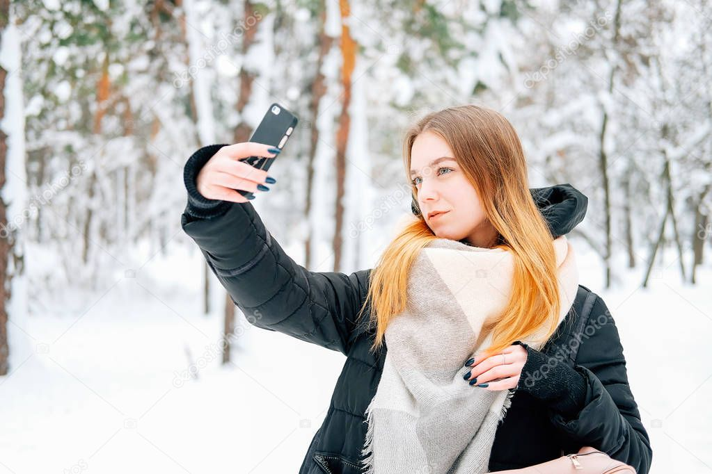 Attractive blond young adult woman walking through winter forest full of snow weearintg casual outfit of black parka, jeans, pink leather boots and backpack and beige shawl and texting to friends