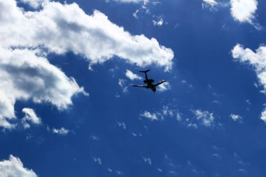 A jet airliner flying under the sun shining in the sky
