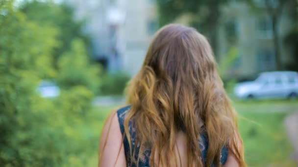 Back view of young woman walking through the street near the tree. Hair waving on wind. The girl turns around. Slow mo.