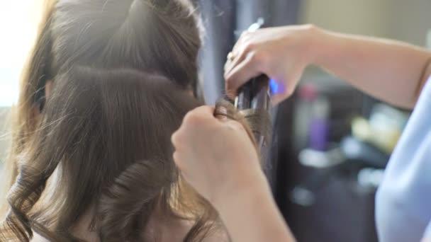 Fodrász teszi az utolsó szakaszban, hogy hozzon létre egy frizura egy aranyos lány, hátulról. Szakmai fodrász stylist teszi a frizura egy aranyos európai kislány a házban.