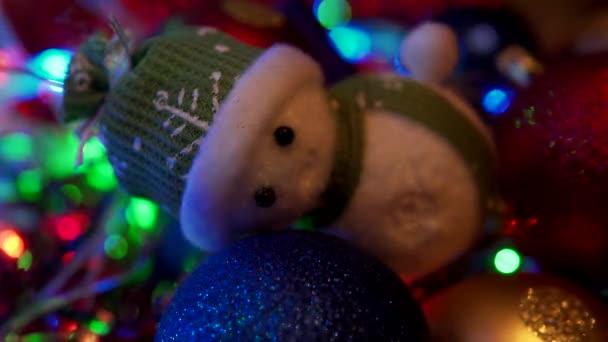 Színes karácsonyi bokeh a villogó sokszínű neon fények és labdák és hóember. Absztrakt homályos háttér zökkenőmentesen és élesen pislákoló Szilveszter rózsaszín kék és zöld piros fények 4k
